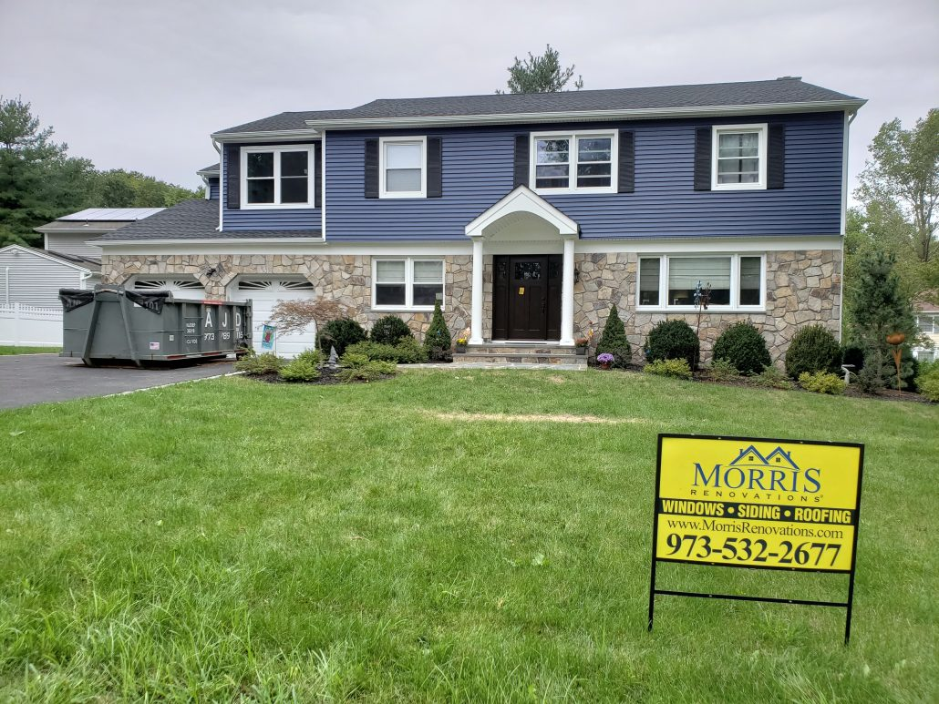 Colonial style house with deep dark blue color vinyl traditional clapboard siding in Whippany NJ Morris County white window trim and white corners morris renovations job sign in front of the house