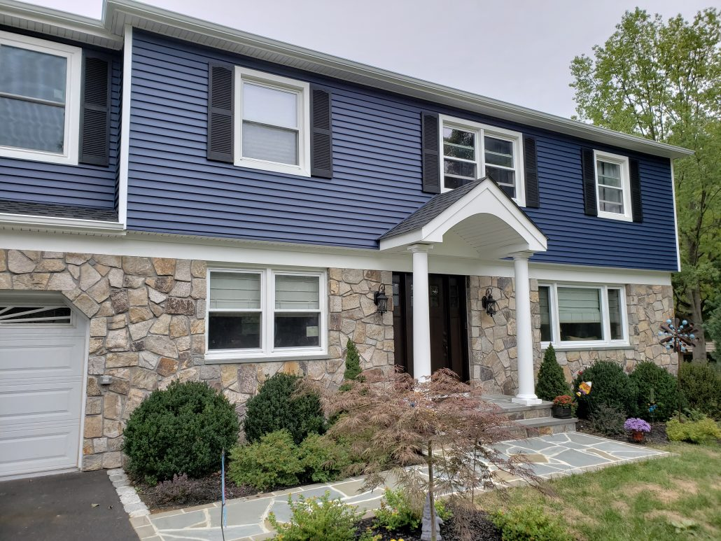 Colonial style house with deep dark blue color vinyl traditional clapboard siding in Morristown NJ Morris County white window trim and white corners