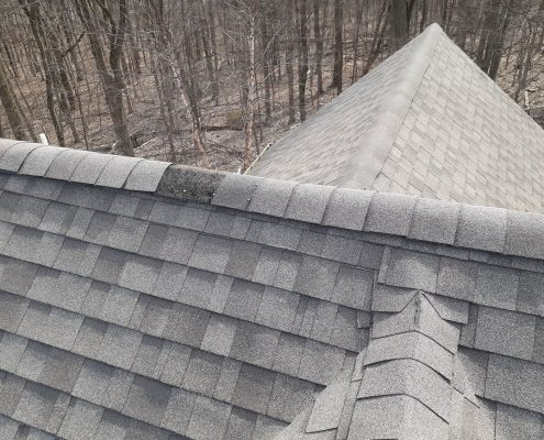 roof that has 3 ridges meeting. one of the ridge caps shingles is missing revealing the ridge vent. Signs for emergency roof repair because water can enter the house through the roof.