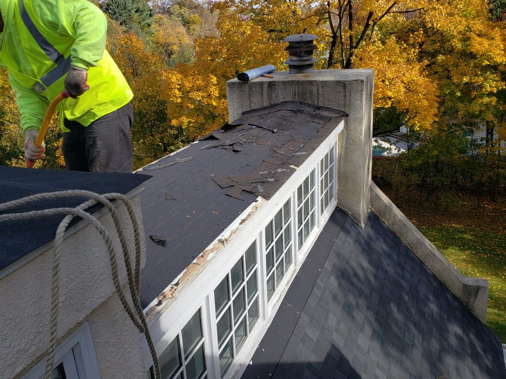 Morristown roofer worker is removing roofing materiial from the roof prior to installing new shingles.